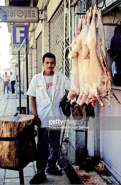 Portrait of a butcher with goat carcasses outside a butcher shop in Amman Jordan