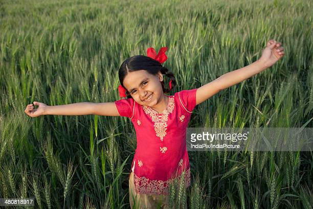 Portrait of a carefree little girl standing with arms outstretched in wheat field