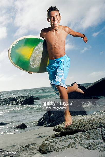 Portrait of a Carefree Teenage Boy Running Along the Beach, Carrying a Surfboard
