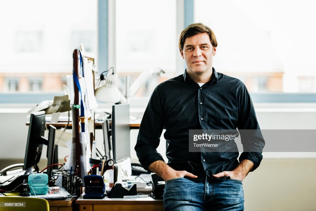 Portrait of a casual businessman standing in an office : Stock Photo
