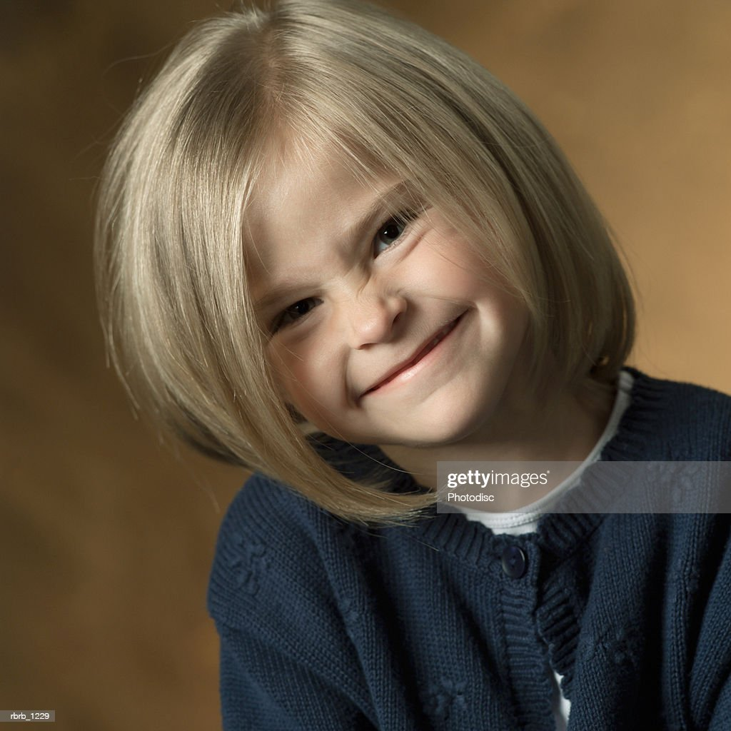 portrait of a caucasian blonde female child in a blue shirt as she smiles slightly : Stockfoto