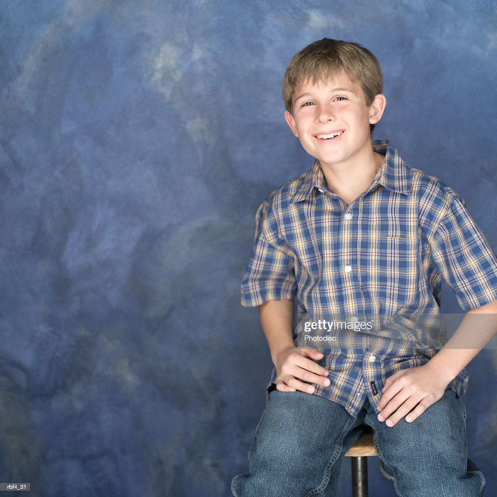 portrait of a caucasian boy in jeans and a plaid shirt rests his hands on his legs looks forward and smiles : Stockfoto