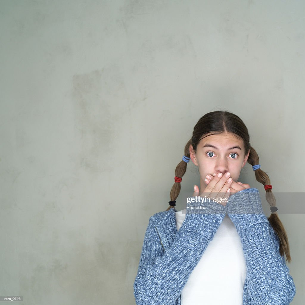 portrait of a caucasian female teen as with pigtails as she covers her mouth in shock : Stockfoto