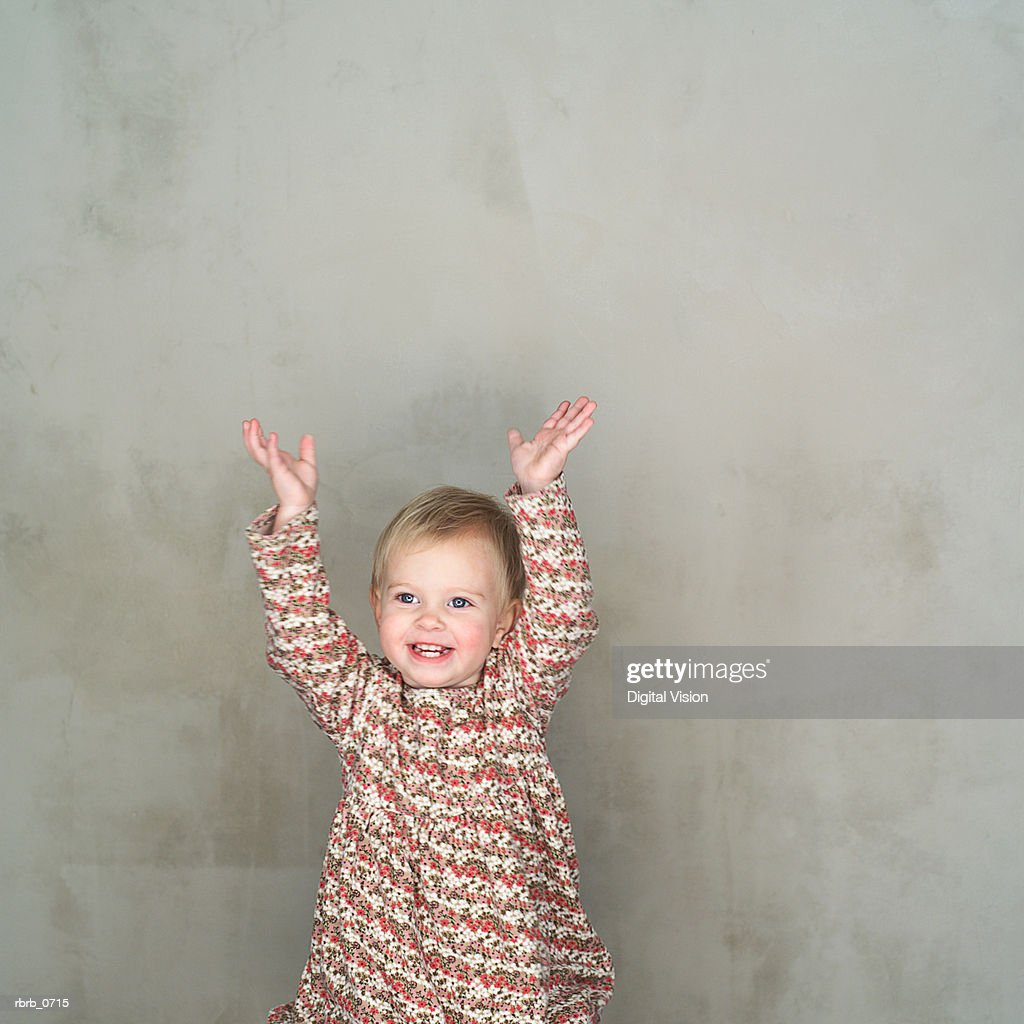 portrait of a caucasian female toddler as she through her arms up : Stockfoto
