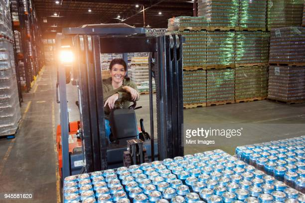 Portrait of a Caucasian female warehouse worker on a forklift in a warehouse full of pallets of flavored water in cans.