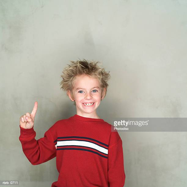 portrait of a caucasian male child in a red shirt as he points upward and smiles