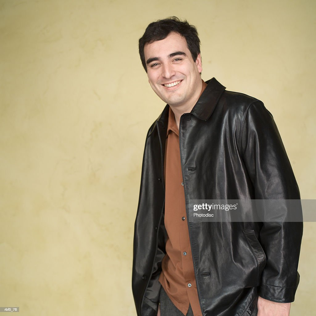 portrait of a caucasian man in an orange shirt and leather jacket as he puts his hands in his pockets and smiles : Stockfoto