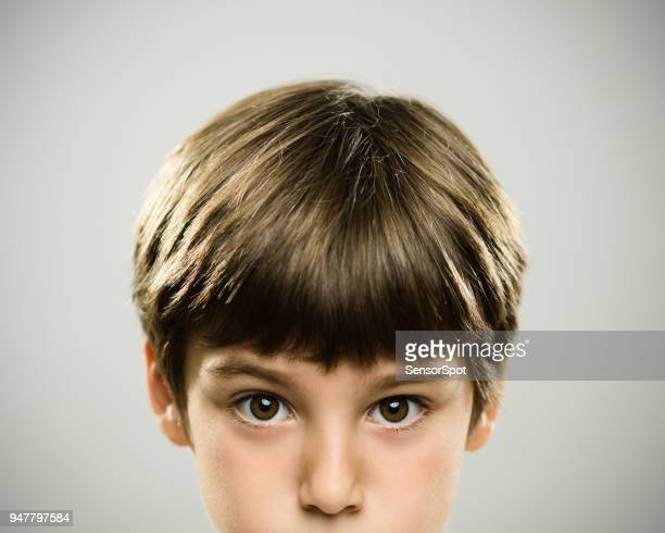 Portrait of a caucasian real boy with serious expression.