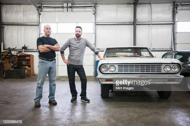 a portrait of a caucasian senior car mechanic and his son in their classic car repair shop. - vintage car stock pictures, royalty-free photos & images
