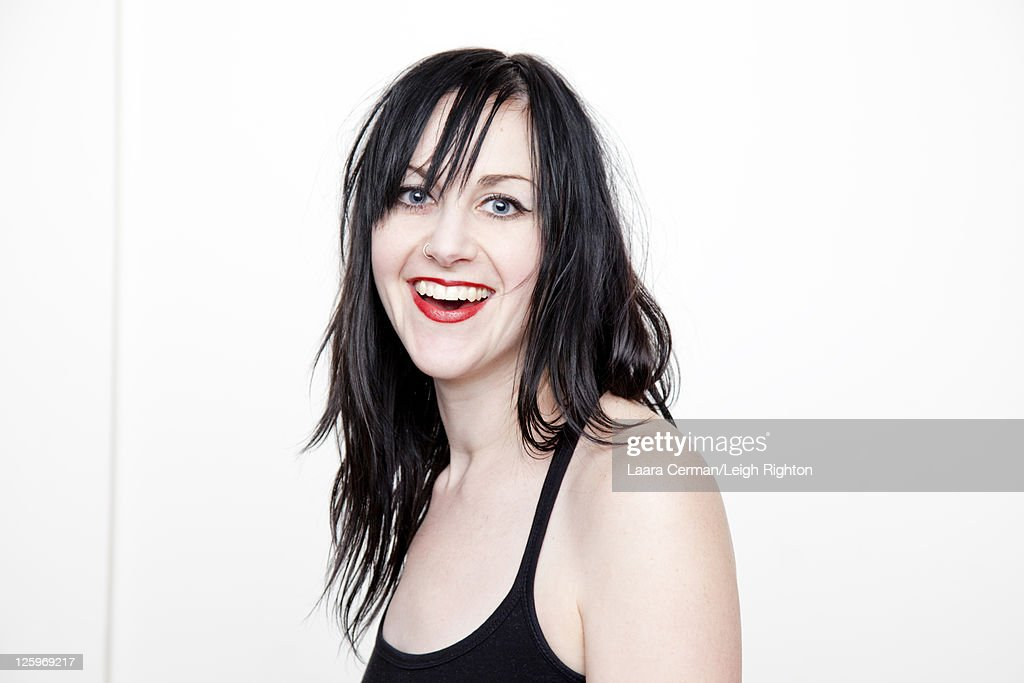 Portrait of a Caucasian woman (28 years old) smiling in front of a white background : Stock Photo