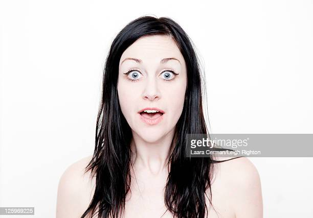 Portrait of a Caucasian woman (28 years old) with surprise expression in front of a white background