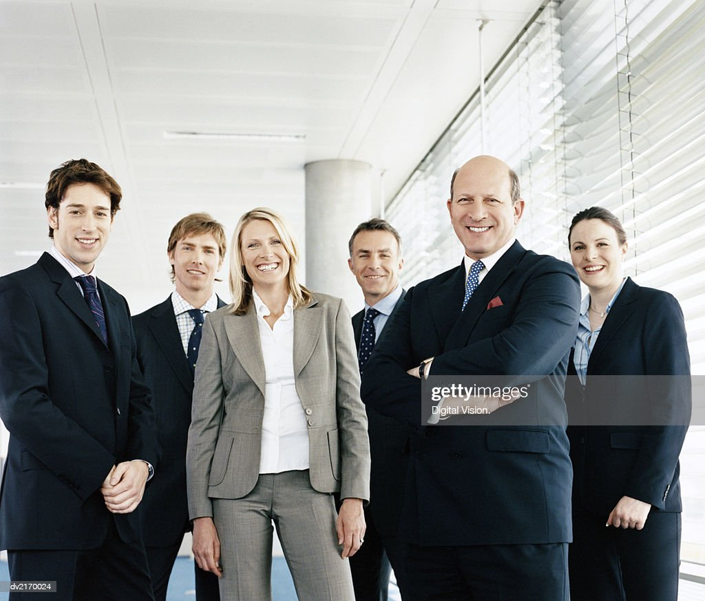Portrait of a CEO With His Team of Business Executives Standing by a Window : Stock Photo
