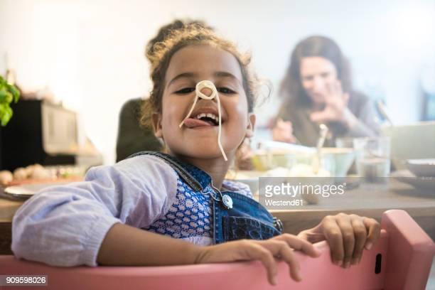 portrait of a cheeky little girl eating spaghetti - spaghetti stockfoto's en -beelden