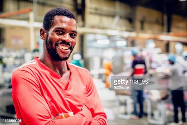 retrato de un trabajador de la fábrica de africa alegre - africano nativo fotografías e imágenes de stock