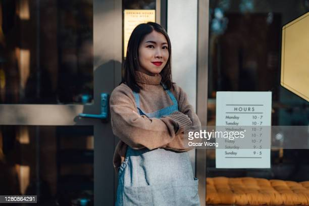portrait of a cheerful and confident female shop owner - winning stock pictures, royalty-free photos & images
