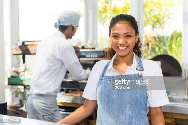 Porträt von einer fröhlichen Barista und ihre Mitarbeiter arbeiten im Hintergrund