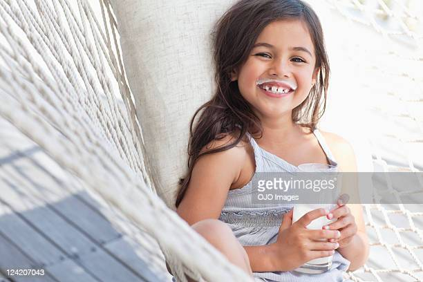 Portrait of a cheerful cute girl smiling holding a glass of milk