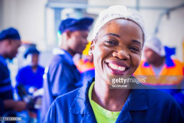 portrait of a cheerful female african factory worker - north africa stock photos and pictures
