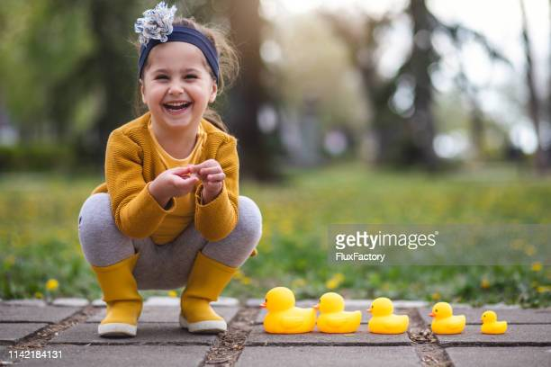 portrait of a cheerful girl with a family of rubber duck toys - duck bird stock pictures, royalty-free photos & images