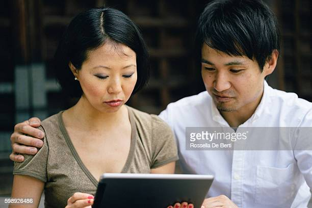 portrait of a cheerful japanese couple using tablet outdoors - adult videos japan stock pictures, royalty-free photos & images