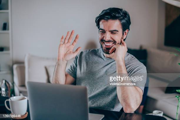 portrait of a cheerful man having video call at home. - greeting stock pictures, royalty-free photos & images