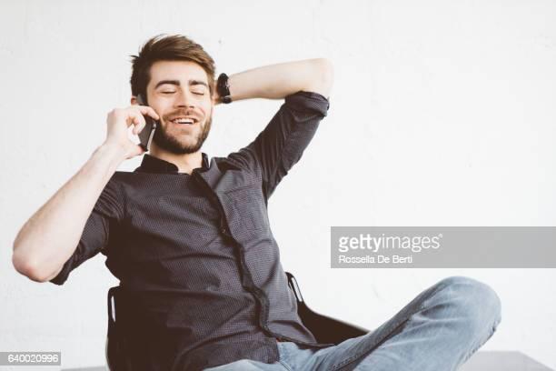 """Portrait de la joyeuse jeune homme au téléphone à l """"intérieur"""
