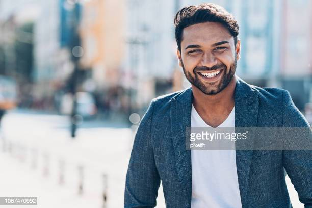 portrait of a cheerful young middle-eastern ethnicity man - modern manhood stock pictures, royalty-free photos & images