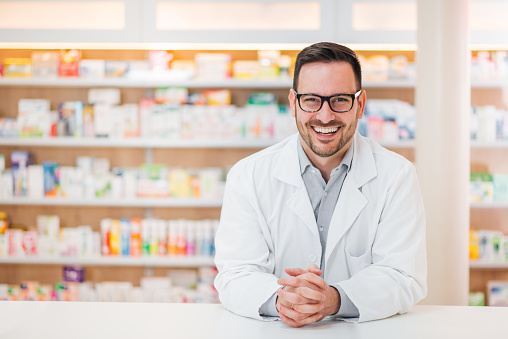Portrait of a cheerful young pharmacist leaning on a counter at drugstore, looking at camera. 1132087010