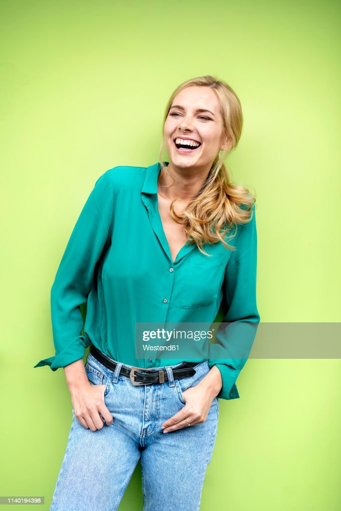 Portrait of a cheerful young woman, against green background : Stock-Foto