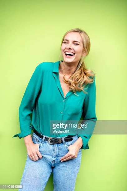 portrait of a cheerful young woman, against green background - lachen stock-fotos und bilder