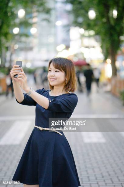 Portrait of a cheerful young woman outdoors using phone