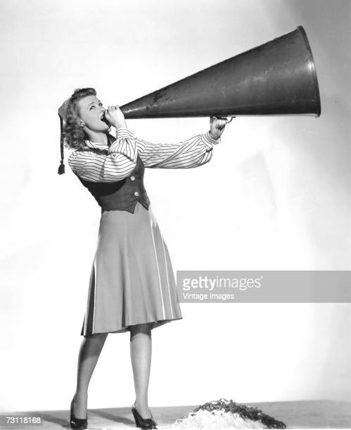 Portrait of a cheerleader as she shouts into a large megaphone while her pomspoms lie on the ground in front of her 1930s or 1940s