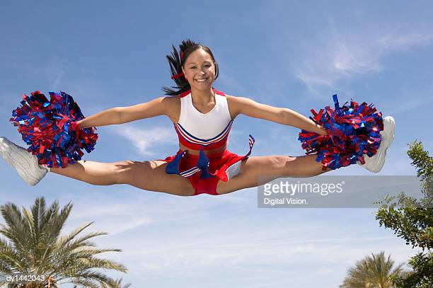 portrait of a cheerleader holding pompoms doing the splits mid-air - cheerleaders stock photos and pictures
