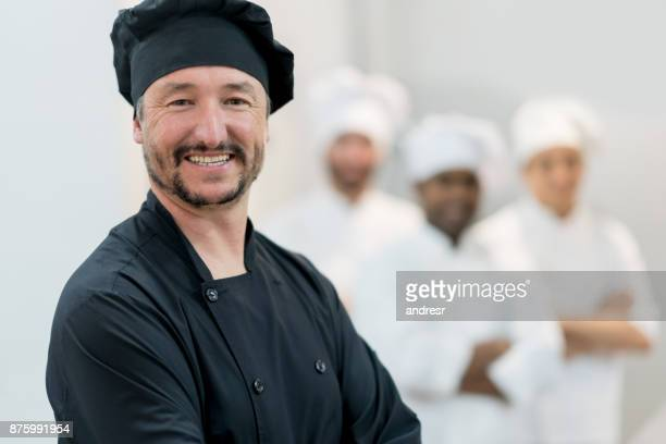 Porträt von Küchenchef Unternehmer ein Restaurant und Blick auf die Kamera zu Lächeln