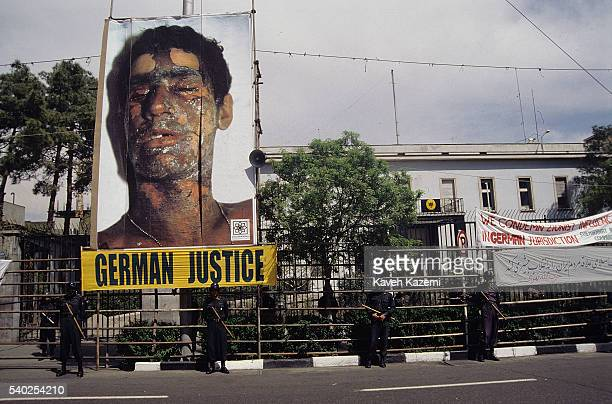 A portrait of a chemical attack victim by Saddam Hussein hangs outside the German embassy protected by security forces where an anti Germany...