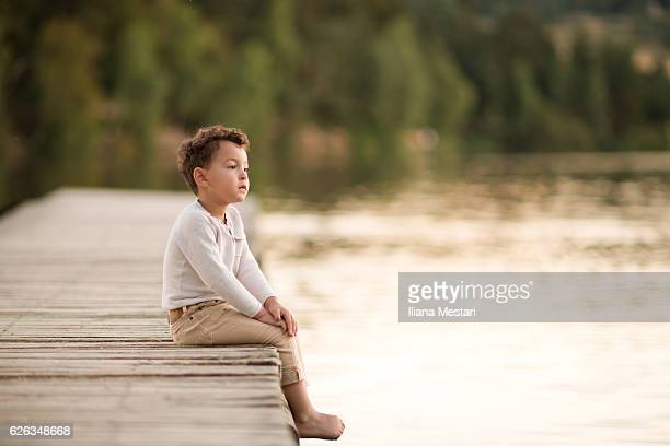 portrait of a child sitting on a dock - september stock-fotos und bilder
