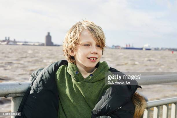 portrait of a child standing by the river mersey - sally anscombe stock pictures, royalty-free photos & images
