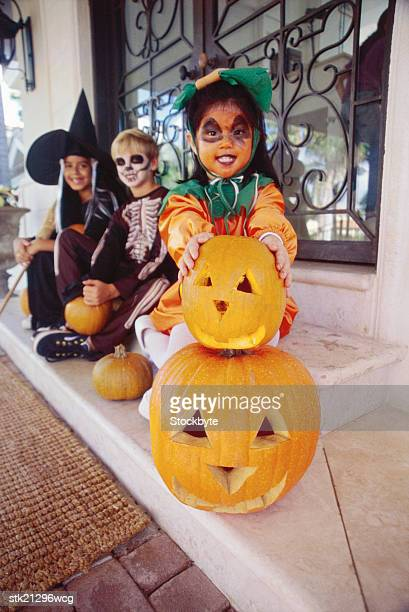 portrait of a children in Halloween costumes sitting behind carved pumpkins