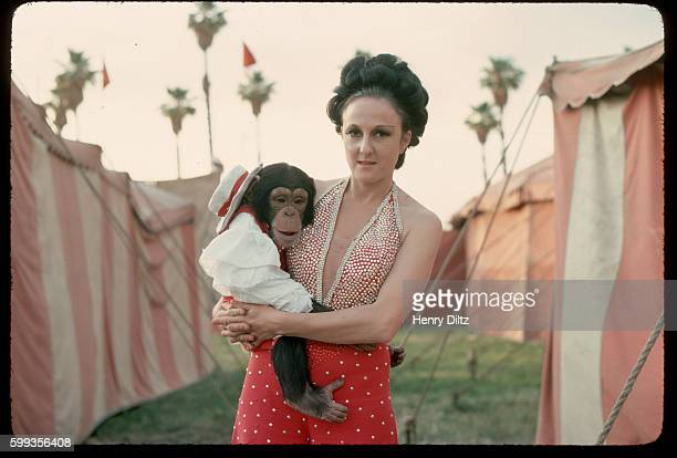 Portrait of a Circus Vargas performer holding a baby chimpanzee during the circus' annual appearance in the Los Angeles area