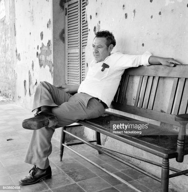 A portrait of a civilian as he sits in front of a building occupied by armed guerrillas from the People's Liberation Forces during an attack in...