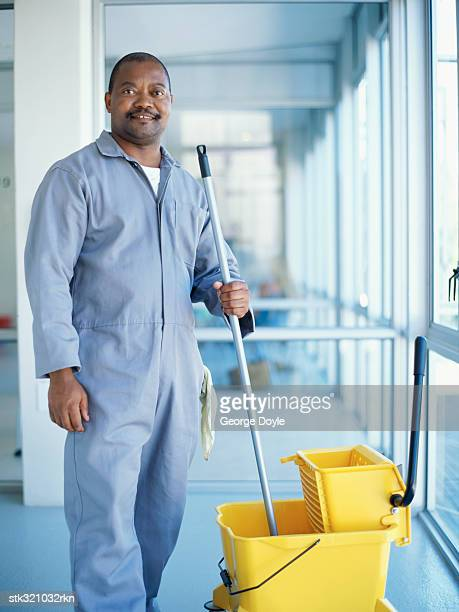portrait of a cleaner holding a mop in an office