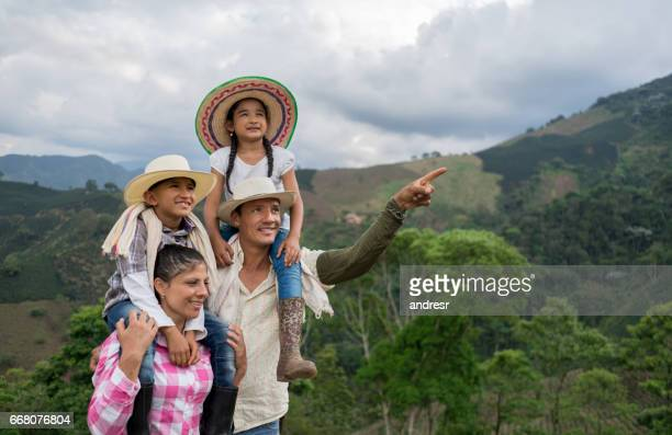 Portrait of a Colombian family pointing away at a farm
