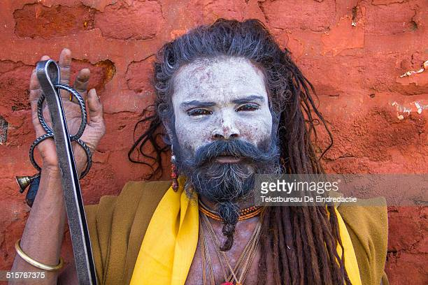 Portrait of a colorful hindu sadhu with long dreadlocks and a white painted face posing before a red wall at the temples of Pashupatinath near...