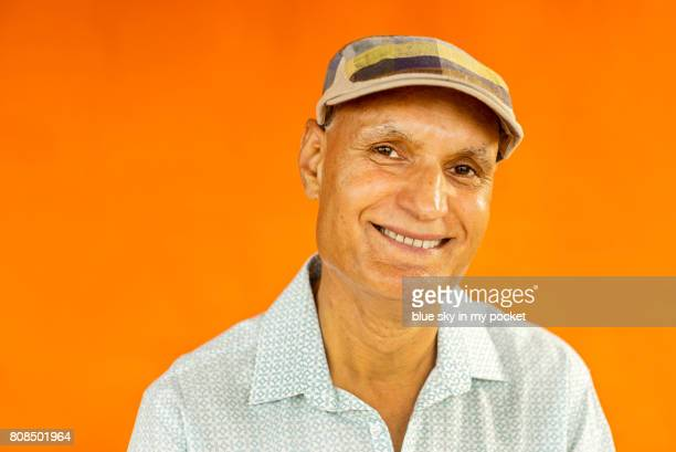 a portrait of a colourful senior asian man. - orange background stock pictures, royalty-free photos & images
