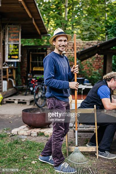 Portrait of a community gardener with rake