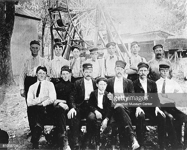 Portrait of a Coney Island Park work crew as they pose before a Ferris wheellike amusement park ride Cincinnati Ohio late 19th century George...