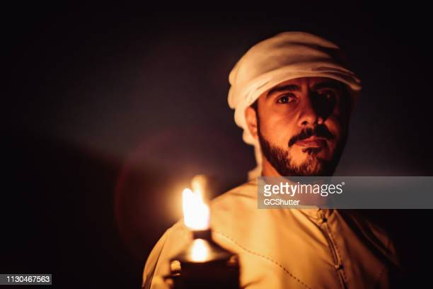 portrait of a confident arab man near an oil lamp - uae heritage stock photos and pictures