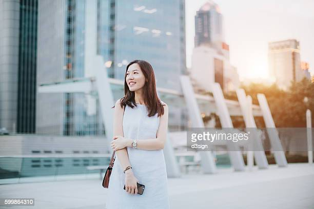 Portrait of a confident Asian woman holding smartphone on hand standing against financial skyscrapers in the city