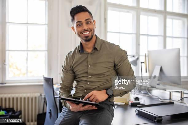 portrait of a confident businessman at his desk - businessman stock pictures, royalty-free photos & images