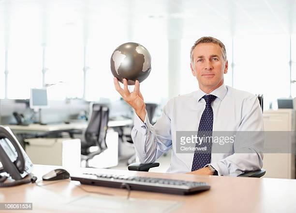 Retrato de un hombre de negocios sosteniendo un globo de confianza